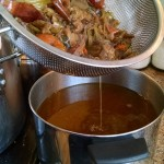 separating veg scraps and bones from broth liquid